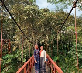 Crossing the red bridge in Bogor Botanical Garden